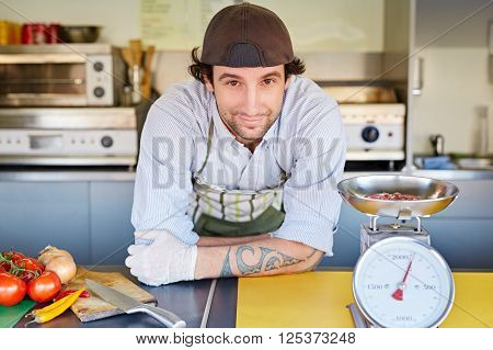 Food entrepeneur looking pleased with his fresh top-quality minced hamburger meat that he weighing in a retro kitchen scale