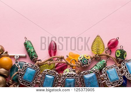 High Angle Still Life Close Up View of Handmade Artisan Jewellery on Pink Background with Copy Space - Fashionable and Intricate Bracelets and Necklaces with Colorful Beads Stones and Baubles poster