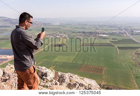 THE VALLEY OF ARAMAGEDDON, ISRAEL - MARCH 27: A man is take a picture of the Armagedon, the place prepared for for a battle during the end times, March, 27, 2016 in The Valley of Armageddon, Israel.