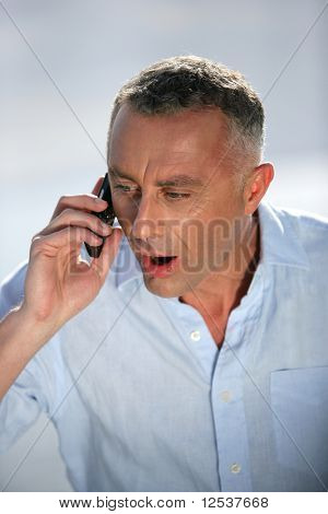 Portrait of a man surprised with a cell phone