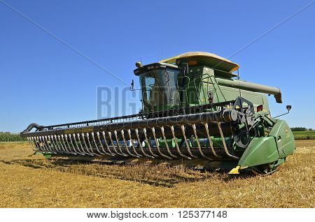 MAYVILLE, NORTH DAKOTA-August 19, 2015: A self propelled combine in a  wheat harvest scene is a  products of John Deere Co, an American corporation that manufactures agricultural, construction, forestry machinery, diesel engines, and drivetrains.