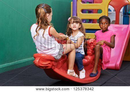 Three children rocking on rocker together at an indoor playground