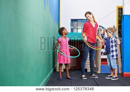 Children and nursery teacher with hula hoops in kindergarten