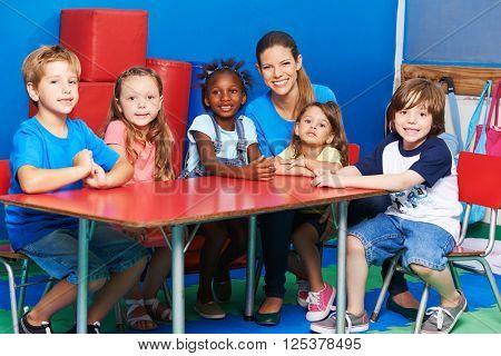 Happy children sitting together with nursery teacher at table in kindergarten
