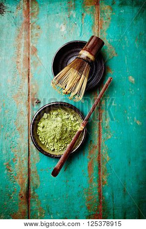 Organic matcha tea and a bamboo tea whisk on a rustic background