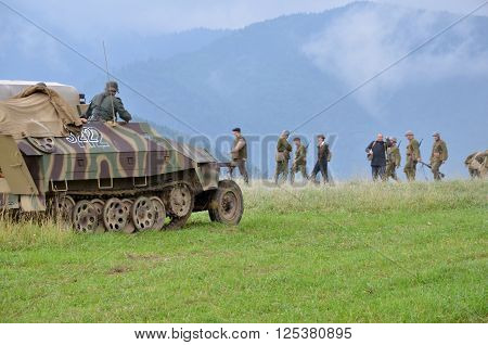 Strecno Slovakia - July 21 2012: Historical reenactment of World War 2 battle - armored transport vehicle and soldiers dressed in german nazi uniforms