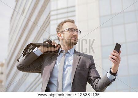 Businessman with a bag over his shoulder holding smart phone in front of the blue glass business building