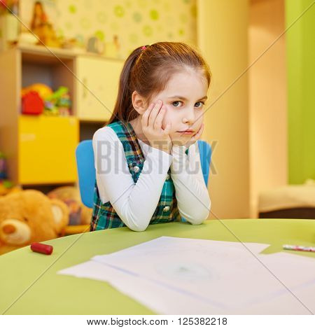 A little girl looking bored of drawing