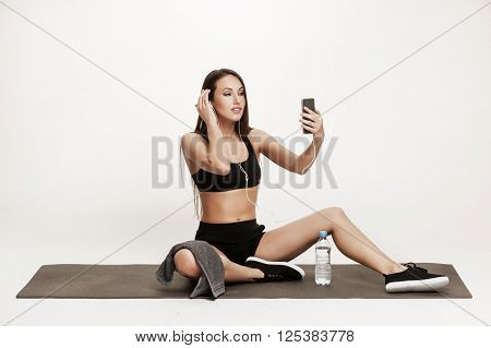 Young woman taking selfie after workout at the gym. Good looking brunette woman in sports outfit. Healthy lifestyle concept.