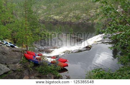 Catamaran tourists on the stones of the mountain river near waterfall