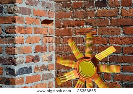 Yellow tin flower and red brick background
