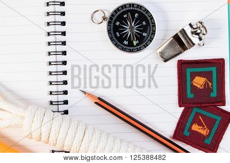 Metal Whistle, Scout Rope, Notebook, Compass, Badge And Pencil On Wooden Table.