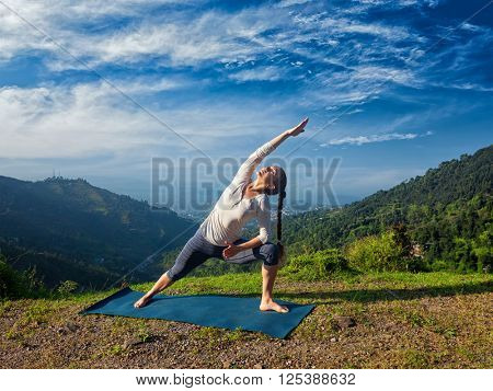 Sporty fit woman practices yoga asana Utthita Parsvakonasana -  extended side angle pose outdoors in mountains in the  morning