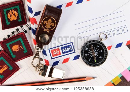 Metal Whistle With Leather Keychain, Compass, Badge On Envelopes Background.