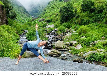 Woman doing Ashtanga Vinyasa yoga asana Utthita trikonasana - extended triangle pose outdoors at waterfall in Himalayas