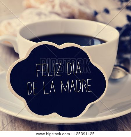 the sentence feliz dia de la madre, happy mothers day in spanish in a blackboard in the shape of a thought bubble placed in a cup of coffee, with some pastries in the background in a set table
