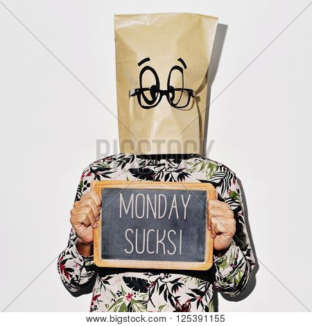 a young caucasian man with a paper bag with a funky face in his head shows a chalkboard with the text monday sucks