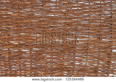 Sunlight peaks through the handmade profusely woven natural fibers of a screen made for protection from the tropical sun. Background.