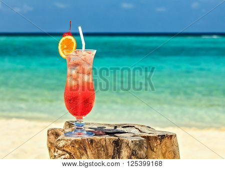 Glass of red drink is on the beach table Maldives The Indian Ocean