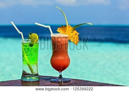 Two glasses of the soft drink are on a beach table (Maldives The Indian Ocean)