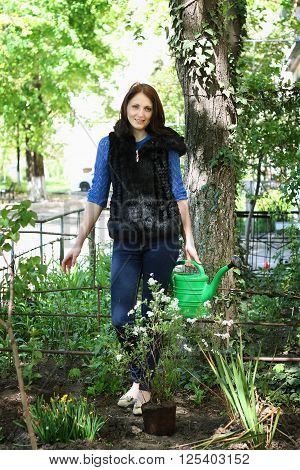 Positive casual dressed woman in yard gardening with watering can