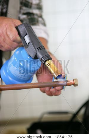 Man warming a metal with a blowtorch