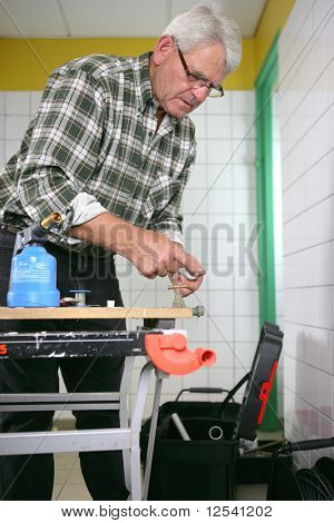 Portrait of a senior man with a blowtorch
