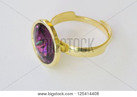 Golden ring with purple gem stone over white