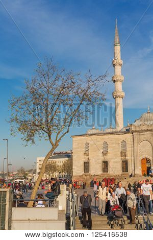 ISTANBUL, TURKEY - APRIL 27, 2015: people walking at Eminonu quarter of Istanbul near Yeni Camil, New Mosque
