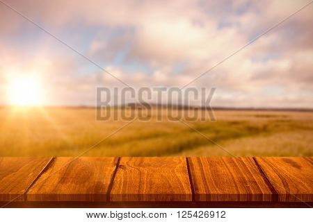 Wooden table against fields backgrounds