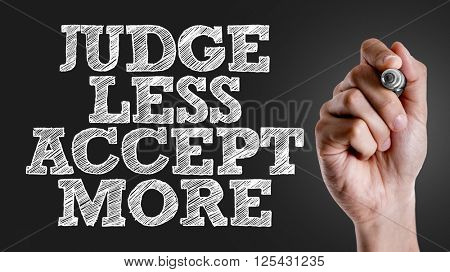 Hand writing the text: Judge Less Accept More
