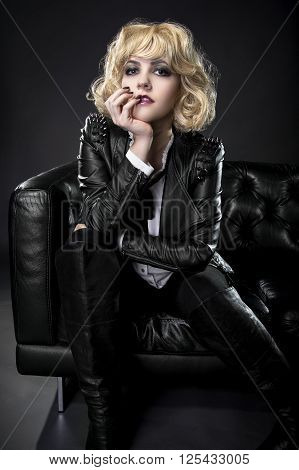 Female dressed in rebellious leather goth rocker style with black nail polish