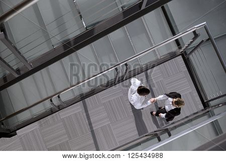 Top view of confindent businessman and woman shaking hands in an office building lobby