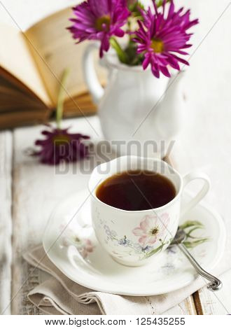 Cup of tea on wooden table and bouquet of flowers
