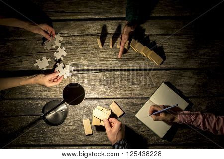 Top view of male and female business colleagues coworking on a project late at night as they take notes stop the falling dominos try to match puzzle pieces and make a construction of wooden pegs.