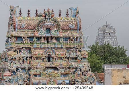 Trichy India - October 15 2013: The dirty-white Vellai Gopuram at the Sri Ranganathar Swamy sanctuary stands in the background of a more common pastel-colored gopuram full of statues including the main Ranganathar depiction of Vishnu resting on the snake.