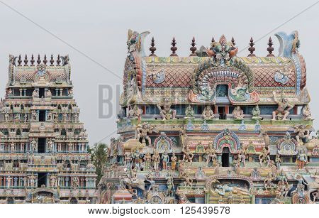 Trichy India - October 15 2013: two gopurams of the temple in one shot pastel colored with plenty of statues including the main Ranganathar depiction of Vishnu resting on the snake.
