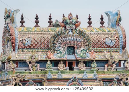 Trichy India - October 15 2013: Closeup of the top of the gopuram called Vimanam shaped as a cake with plenty of statues in pastel colors. Garudas on corners.