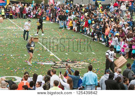 MARIETTA, GA - MARCH 2016: Teen volunteers cover a high school football field with plastic easter eggs and candy as hundreds of local residents wait to begin a massive community easter egg hunt in Marietta, GA on March 26 2016.