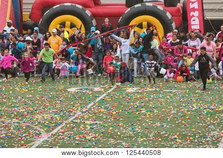 MARIETTA, GA - MARCH 2016: Children and parents eagerly dash out onto the football field at a local high school for the start of a massive community Easter egg hunt in Marietta GA on March 26 2016.