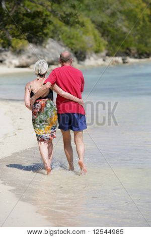 Portrait of a happy senior couple having a walk on the beach