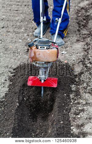 Farmer Prepares Soil For Seeding By Tiller