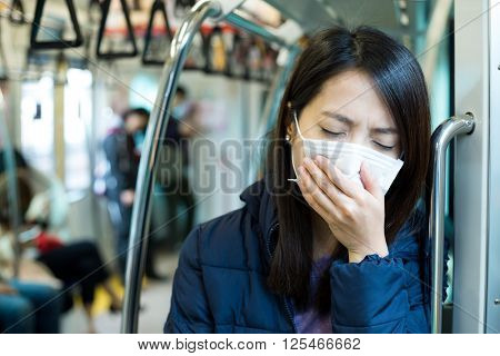 Woman wearing face mask at train compartment