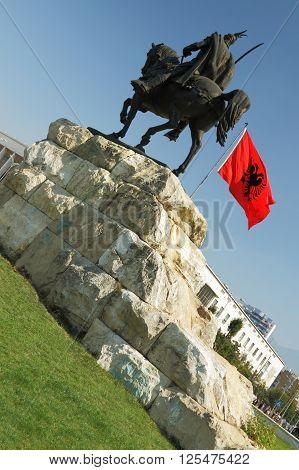 Skanderbeg's monument Tirana Albania and Albanian national flag flying poster