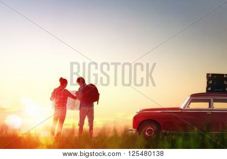 Toward adventure! Man and woman enjoying road trip. Couple searches for a route on the map.