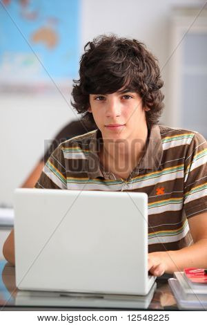 Portrait of a teenager in front of a laptop computer poster