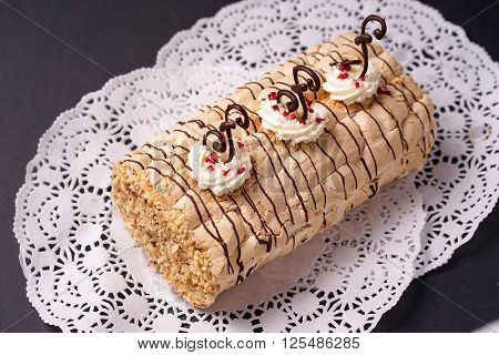 pastry biscuit roulade with whipped cream and chocolate scrolls ready for serving to the teaparty