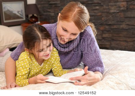 Portrait of a young woman and a little girl stretched out on a bed reading a book