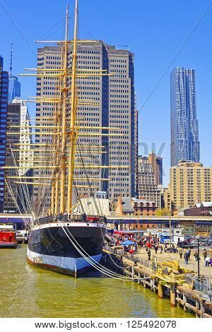 New York, USA - April 25, 2015: Ship in the harbor of South Street Seaport on East River. Lower Manhattan in New York USA is on the background. Pier 17. Tourists around.