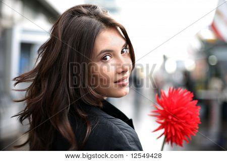 Mooie vrouw met rode bloem Terugkijkend
